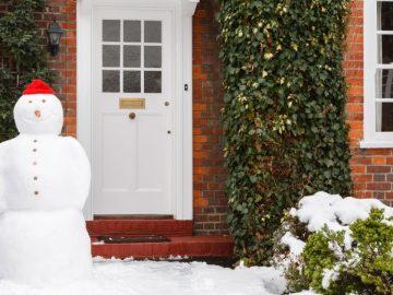Real snowman outside house in winter scene